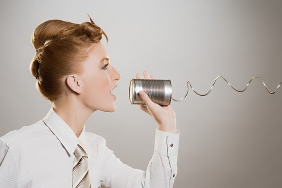 Redheaded woman in business attire speaking through a tin-can phone to an unseen person
