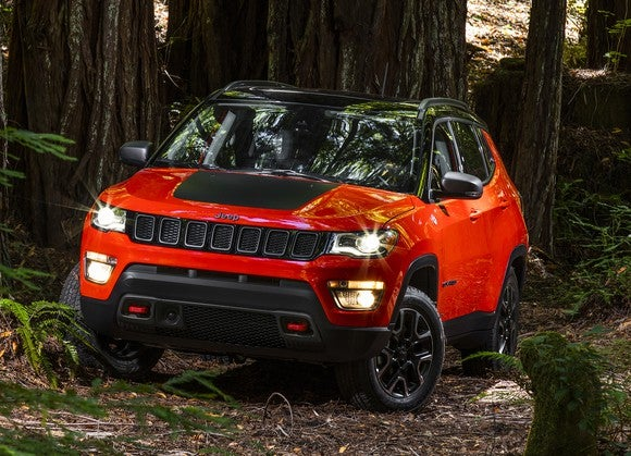 A bright red 2017 Jeep Compass, a compact SUV, on a trail in the woods.