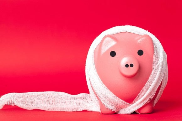 A piggy bank wrapped in bandages, against a red background.