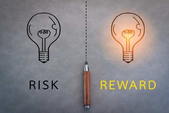 "Drawing of two light bulbs separated by a dotted line with an ink pen. ""Risk"" is written under one bulb while ""reward"" is written beneath the other, which is lit up."