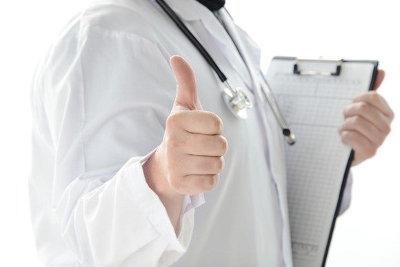 A doctor giving the thumbs-up sign while holding a clipboard.