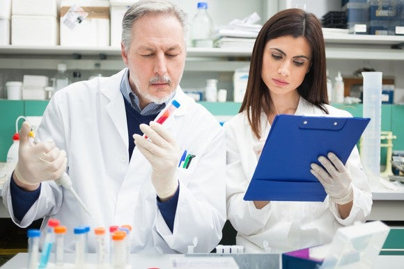 Two biotech lab researchers holding a vial of liquid and making notes on a clipboard.