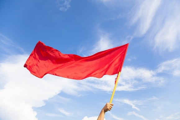 An arm holding up a red flag against a blue sky.