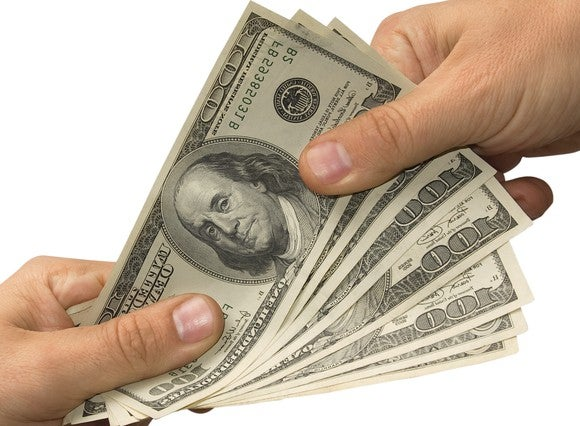 Handing over hundred dollar bills.