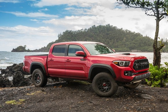 A red 2017 Toyota Tacoma parked by a lake.