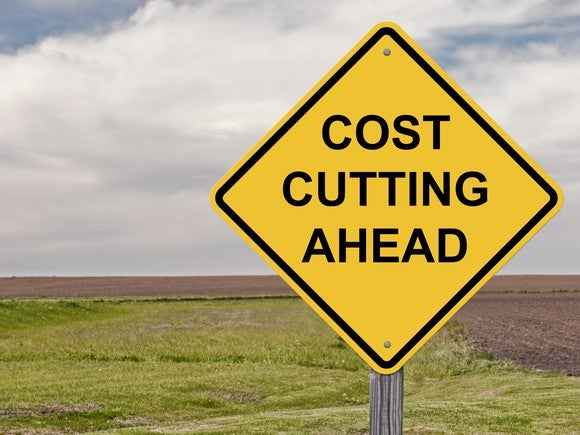 "A yellow road sign that says ""Cost Cutting Ahead."""