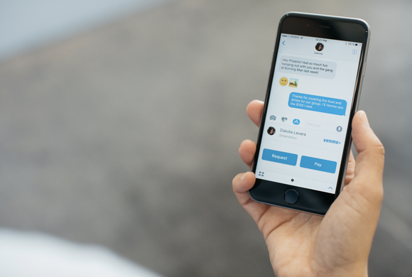 Hand holding smartphone displaying Apple's iMessage app with Venmo integration.