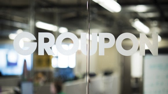 A Groupon logo on a glass office door.