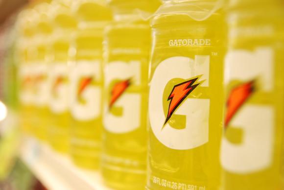 Close up of a row of yellow Gatorade bottles on a store shelf.