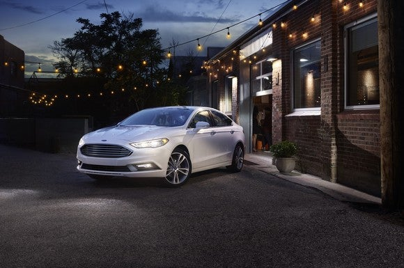 A white Ford 2017 Fusion parked in front of a brick building at night