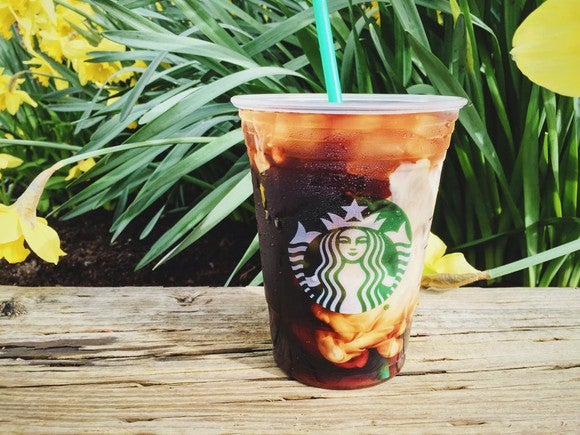A Starbucks iced coffee siting on a wooden surface, with daffodils in the background.