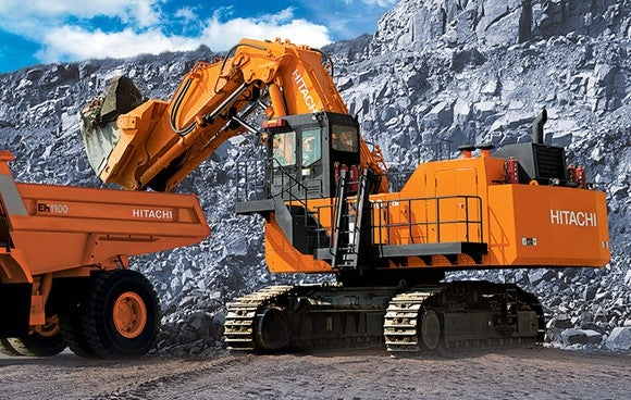 An orange Hitachi excavator and hauler working in a remote mining operation.
