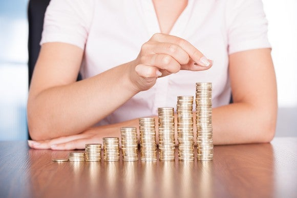 Woman in a white shirt, stacking coins in piles of rising height on a table.