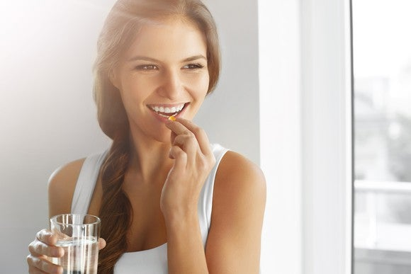 A woman taking a vitamin and holding a glass of water