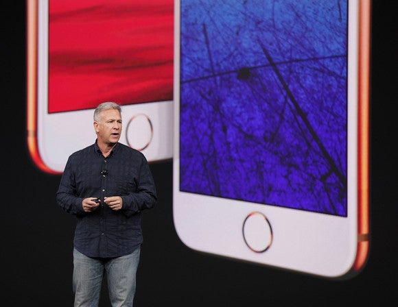 Apple executive Phil Schiller standing in front of images of the new iPhone 8 and iPhone 8 Plus.