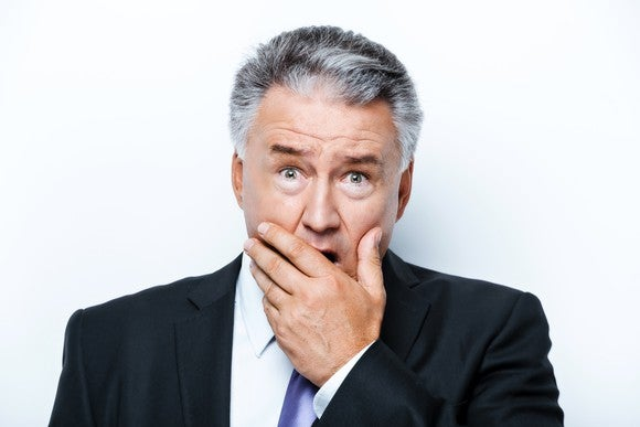 A worried man in a suit covering his mouth in disbelief.
