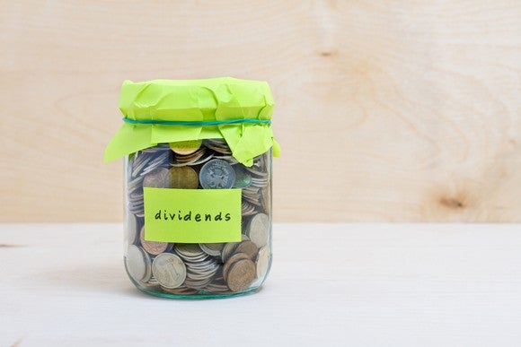 "A jar filled with coins is closed with a rubber band around a piece of paper. The jar is labeled with the word ""dividends."""