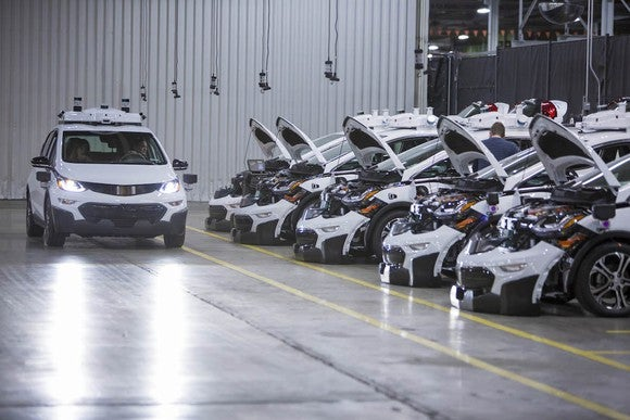 Image of GM cars with hoods open in a factory.