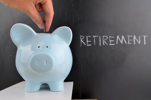 "Coin being inserted into piggy bank in front of a chalk board reading ""retirement"""