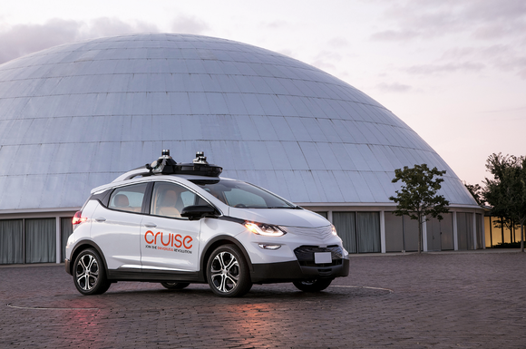 A white Chevrolet Bolt EV with Cruise Automation logos and self-driving sensors visible is parked outside the historic Design Dome at GM's technical center in Warren, Michigan.