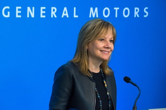 """Mary Barra stands before a blue backdrop with the words """"General Motors"""" visible, during a presentation to GM shareholders on June 6, 2017."""