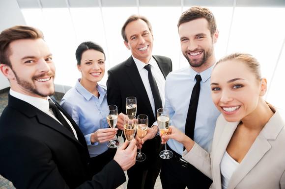 Professionals raising champagne glasses