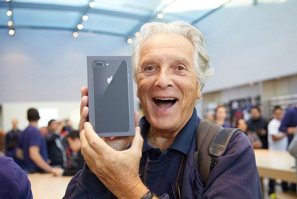 A smiling man holding a new iPhone 8 Plus.