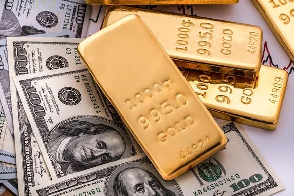 Gold bars lie on top of one hundred dollar bills.