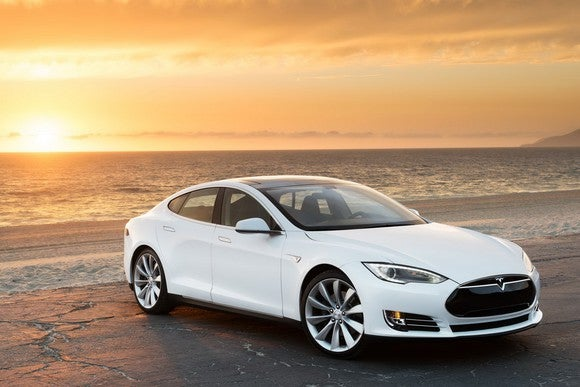A Tesla Model S parked on a beach.