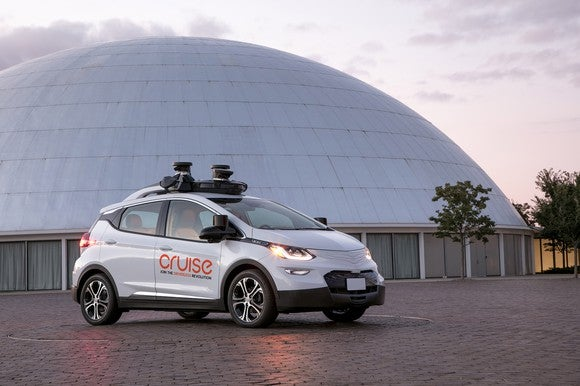 A white Chevrolet Bolt EV with Cruise Automation logos and visible self-driving sensors is parked next to a dome.