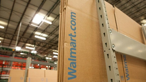 "Flat-packed cardboard boxes with ""Walmart.com"" printed on them sitting in a warehouse."