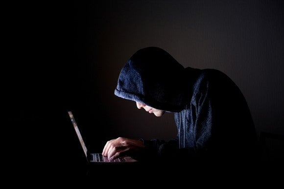 A person in a black hoodie in a dark room, hunched over a laptop with the only light coming from the computer's screen.