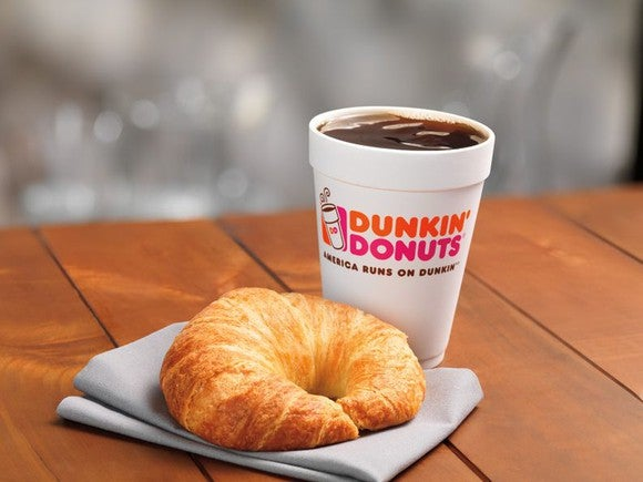 A cup of Dunkin' Donuts coffee and a croissant
