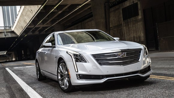A silver 2018 Cadillac CT6, a full-size luxury sedan, on a road under an overpass.