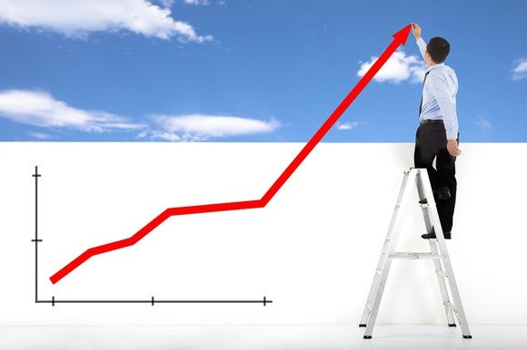 Man standing on ladder drawing a chart going up.