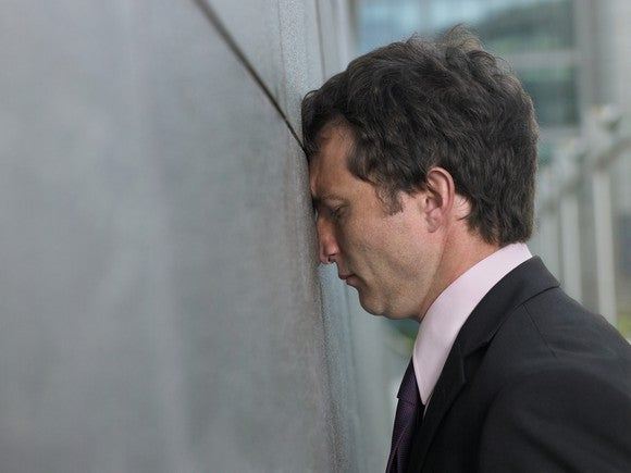 Business man leans his head against the wall.