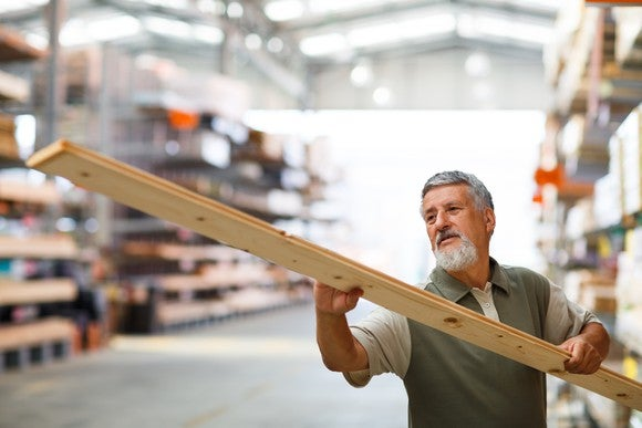 A shopper inspects a piece of lumber at a home improvement warehouse.