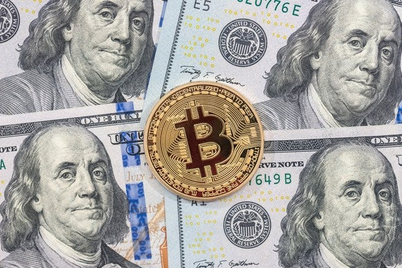 A physical gold bitcoin lying atop hundred dollar bills.