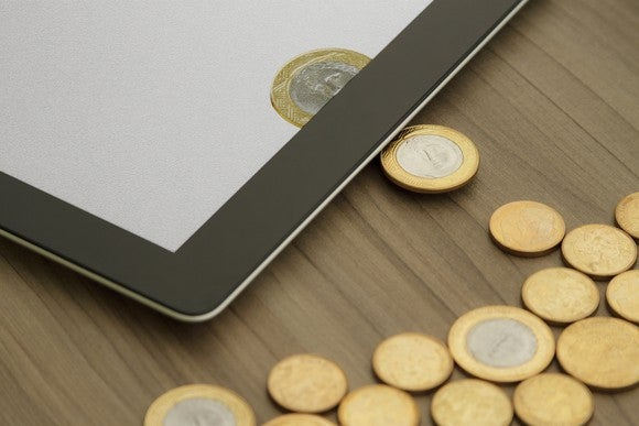 Physical coins changing into digital coins on a tablet.