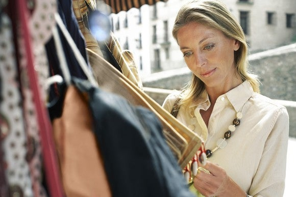 A woman looking at clothes on a sales rack.
