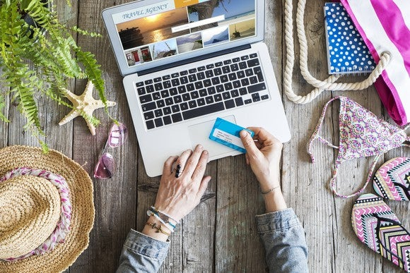 A woman booking travel online with a credit card in hand on top of a wooden table with beach gear laid out.