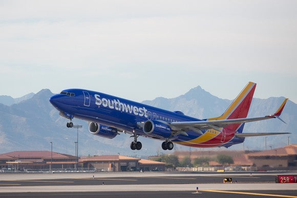 A Southwest Airlines plane taking off, with mountains in the background.