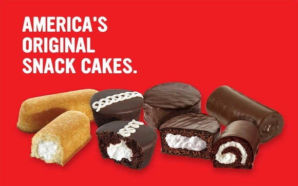 """Twinkies, Ding Dongs, Ho-Hos, and cupcakes on a red background with """"America's Original Snack Cakes"""" caption."""