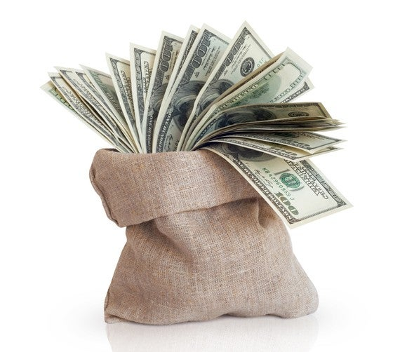 Multiple hundred dollar bills coming out of a burlap bag.