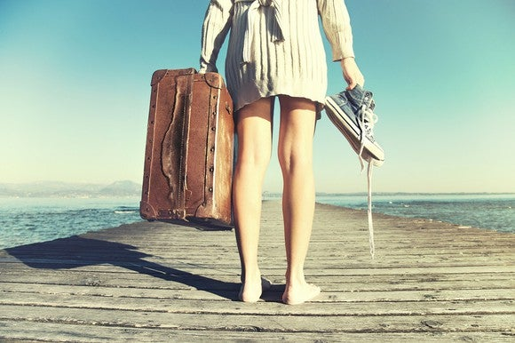 Woman on dock holding a suitcase in one hand and shoes in the other