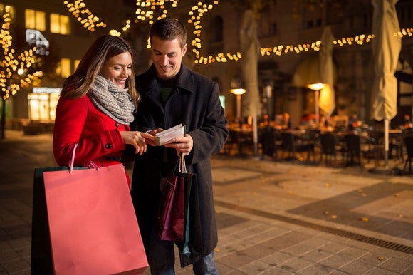 Photo of two people in winter clothes looking at a shopping list of gifts.