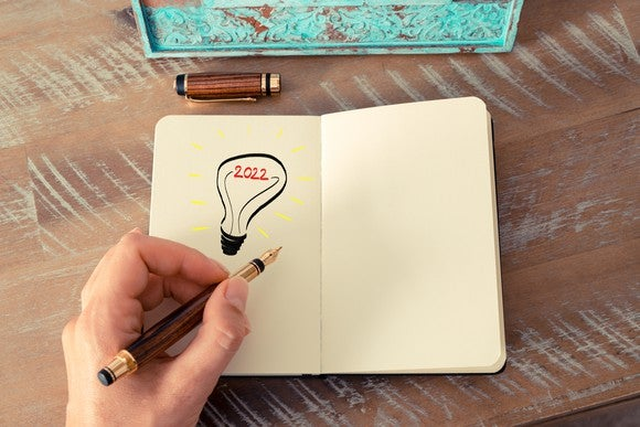 Hand holding pen over notepad with picture of light bulb with 2022 drawn on it