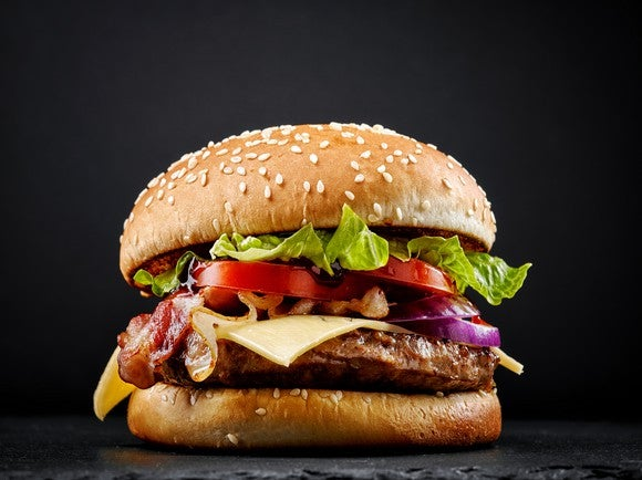 Bacon cheeseburger on a black background.
