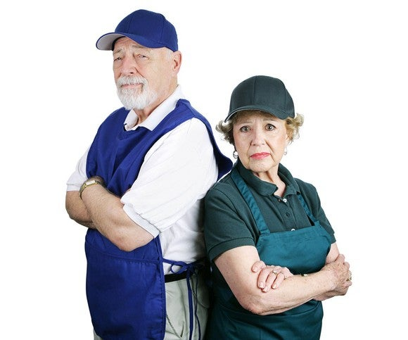 Older man and woman dressed for work with frowns.
