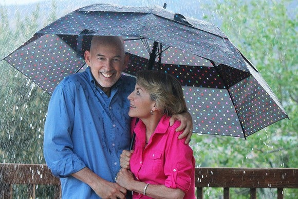 Smiling older couple stand under an umbrella in the rain.